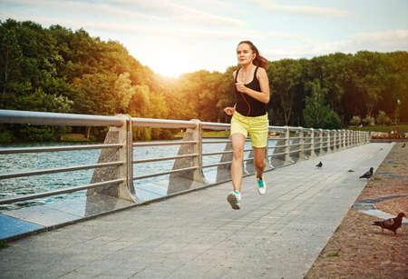 jogging: Pretty sporty woman jogging at park in sunrise light