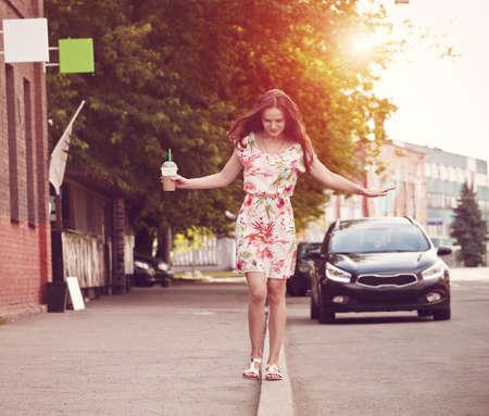 pretty smiling girl with milk shake walking at morning street 스톡 콘텐츠