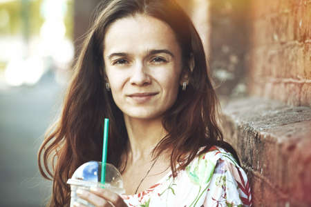 shake off: Portrait of pretty girl with milk shake at morning street Stock Photo
