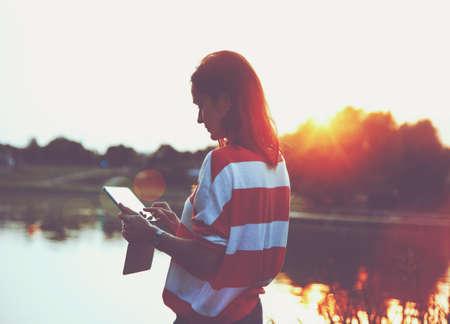 usando computadora: muchacha que sostiene el PC tableta digital en la orilla del lago en la luz del amanecer