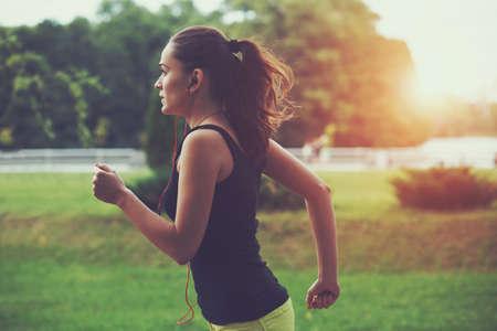 漂亮的運動型的女人在公園的日出光慢跑