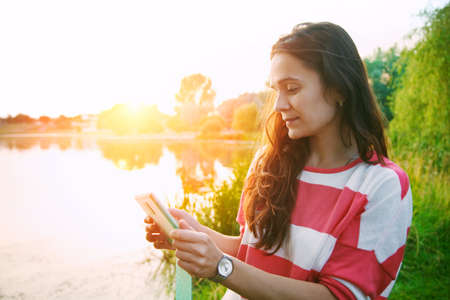woman sunset: girl holding digital tablet pc at lake shore in summer sunrise light