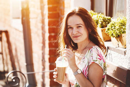 shake off: pretty smiling girl with milk shake sitting on bench at street cafe Stock Photo