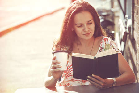 erudition: smiling girl sitting at summer terrace in street with morning coffee and reading book