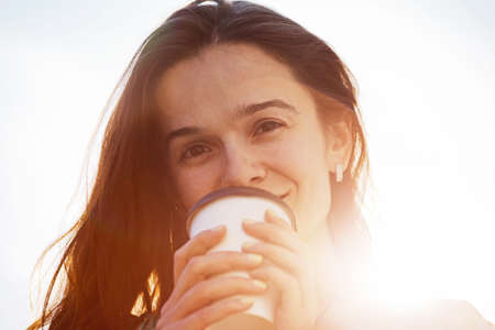 smiling pretty girl with morning coffee in sunlight photo