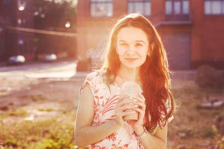 pretty smiling girl with milk shake walking at morning street photo