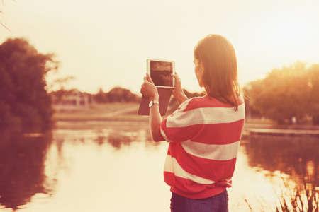 girl holding digital tablet pc taking photo at lake shore in sunrise light photo