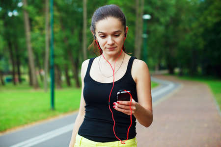 Pretty smiling woman jogging at park with smartphone app and music photo