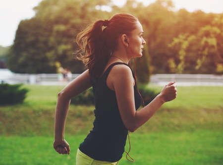 Pretty sporty woman jogging at park in sunrise light photo