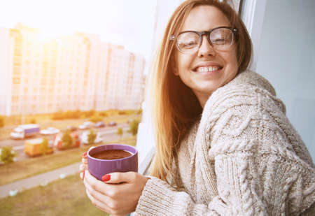 balcony window: cheerful girl drinking coffee in morning sunlight in open window