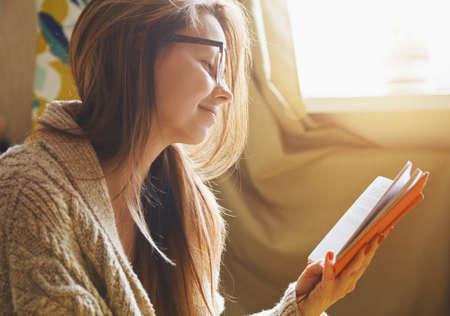 descansando: ni�a de leer el libro en casa en la ma�ana la luz del sol