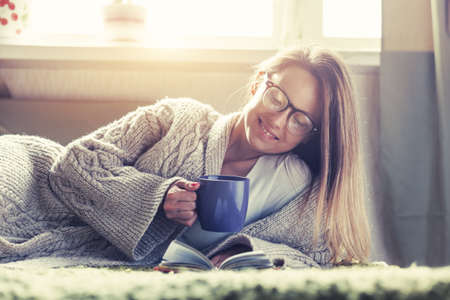 pretty girl reading book with morning coffee lying in bed Stockfoto