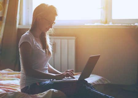 漂亮的女人與筆記本電腦坐在床上在早晨的陽光和打字