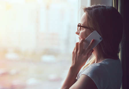 mooie vrouw praten over de telefoon in de buurt raam thuis in de ochtend zonlicht