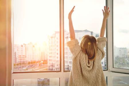 leuchtend: Frau in der Nähe von Fenster, die Hände anheben mit Blick auf den Sonnenaufgang am Morgen
