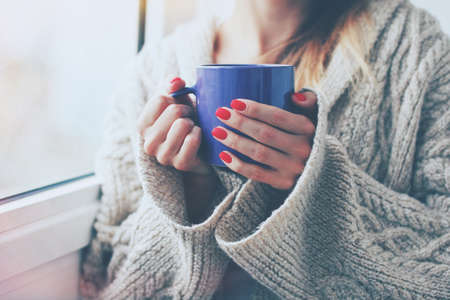 cold woman: hands holding hot cup of coffee or tea in morning