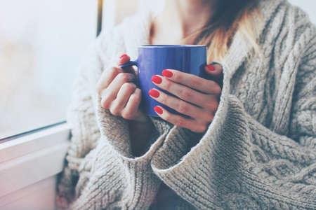 freddo: mani che tengono calda tazza di caffè o tè di mattina Archivio Fotografico