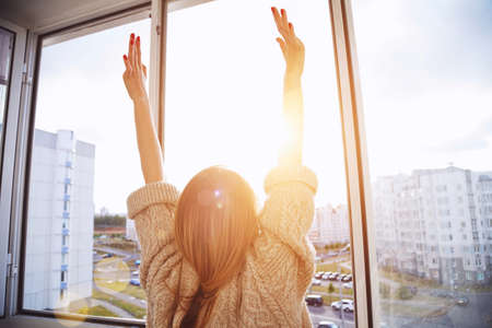 Woman near window raising hands facing the sunrise at morning