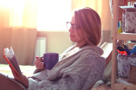 mujer leyendo libro: bonita niña leyendo el libro con café Foto de archivo
