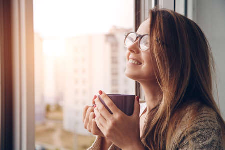 morning: cheerful girl drinking coffee or tea in morning sunlight