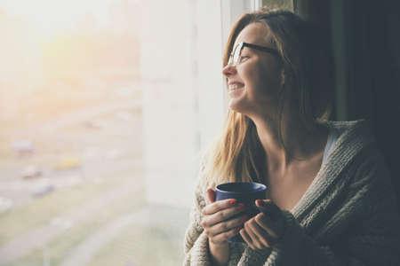 Alegre café o té de consumición de la muchacha en el sol de la mañana cerca de la ventana Foto de archivo - 47499492