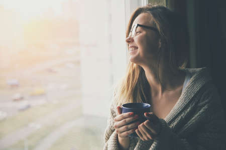 cheerful girl drinking coffee or tea in morning sunlight near window Stock Photo