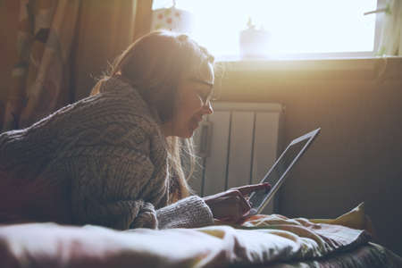 girl lying bed: woman lying in bed with digital tablet touching with finger in morning sunlight