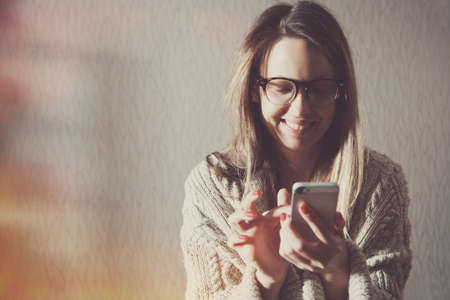 pretty woman with smartphone touching screen and using app