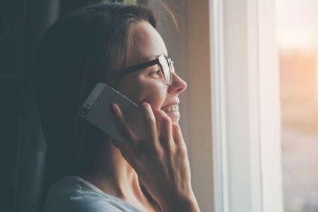 hablando por telefono: bonita mujer hablando por teléfono cerca de la ventana en casa Foto de archivo