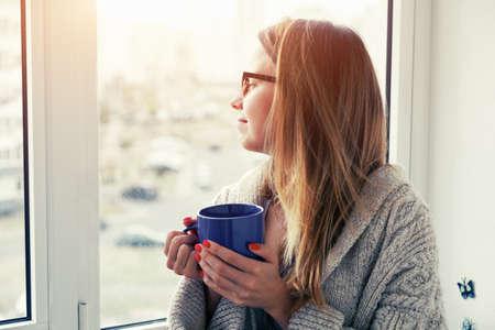 cheerful girl drinking coffee or tea in morning sunlight near window 免版税图像