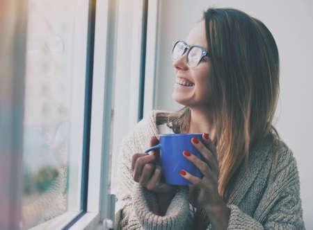 Alegre café o té de consumición de la muchacha en el sol de la mañana cerca de la ventana Foto de archivo - 46806327