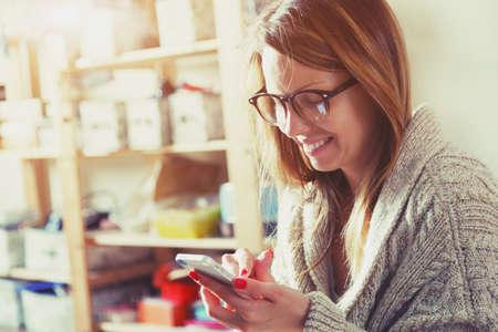 漂亮女人與智能手機的觸摸屏,並使用應用程序