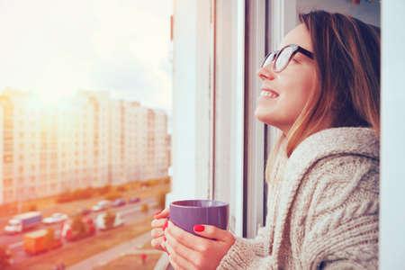 開朗的女孩喝咖啡的早晨的陽光在打開的窗口