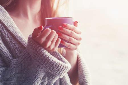 Manos sosteniendo taza caliente de café o té en la mañana Foto de archivo - 57077238