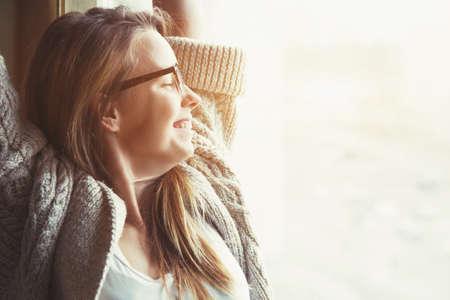 Femme près d'une fenêtre à main levée face au lever du soleil au matin Banque d'images - 57077244