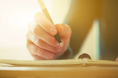 persona escribiendo: manos de una mujer con lápiz de escribir en el cuaderno