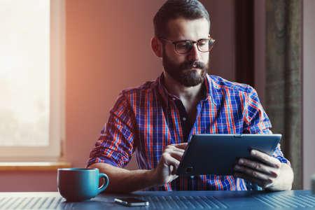 bearded man sitting with cup of morning coffee and digital tablet touching with finger