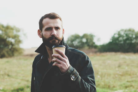 drink coffee: Bearded man with paper cup of morning coffee walking in park Stock Photo