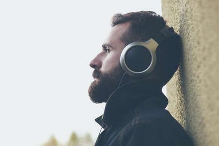 yearning: stylish bearded man  in headphones listening to music