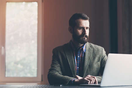 bebaarde zakenman met laptop zitten en werken Stockfoto