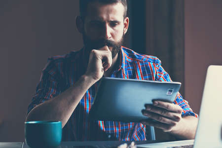 hombre tomando cafe: concentrated bearded man sitting with digital tablet and cup of coffee Foto de archivo