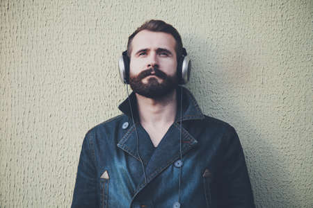 hombre barba: stylish bearded man  in headphones listening to music