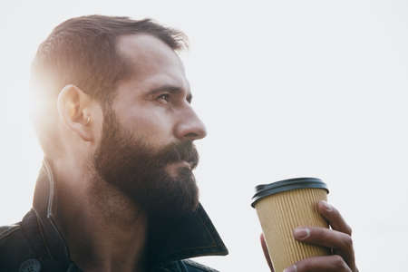 Bearded man with paper cup of morning coffee in sunlight Stockfoto