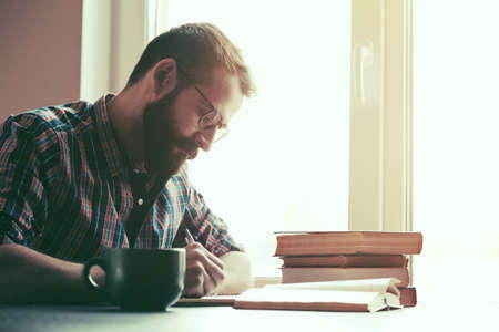 Bearded man writing with pen and reading books at table Stockfoto