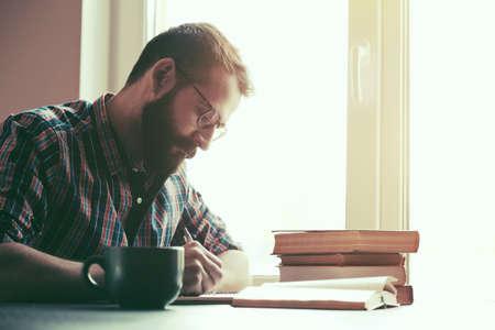 Brodaty mężczyzna pisanie piórem i czytanie książek przy stole