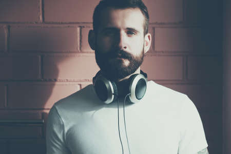 listening device: stylish bearded man in white t-shirt with headphones on brick wall background Stock Photo