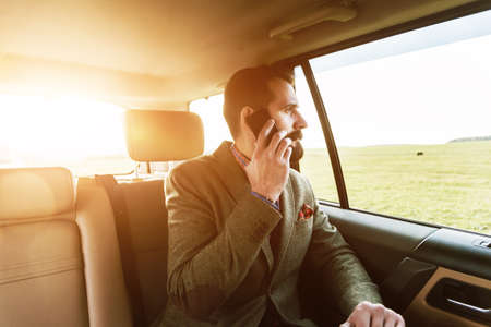 back seat: handsome bearded businessman sitting on back seat of car and talking on phone