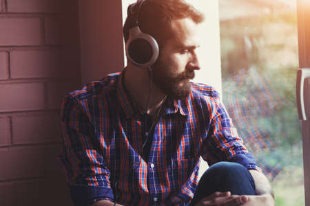stylish bearded man  in headphones listening to music near window with reflection Stock Photo - 59190476