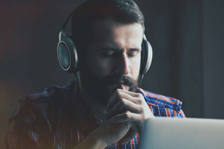 listening device: handsome bearded man  in headphones listening to music with laptop Stock Photo