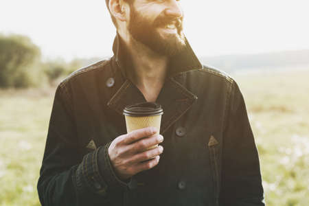 handsome bearded man with paper cup of morning coffee walking in park